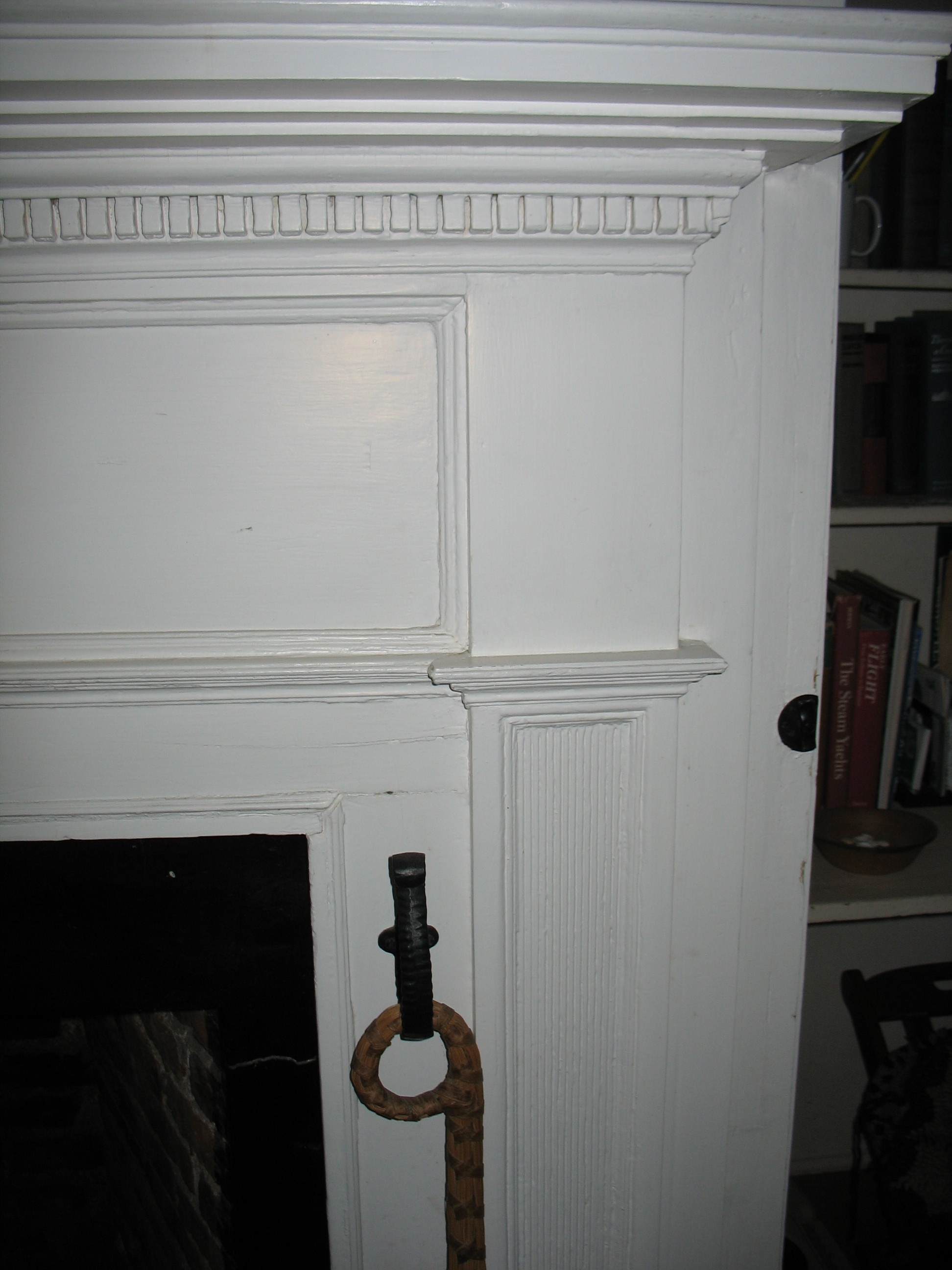 A Federal mantel added in the late eighteenth century containing a decorative dentil band and reeded pilasters