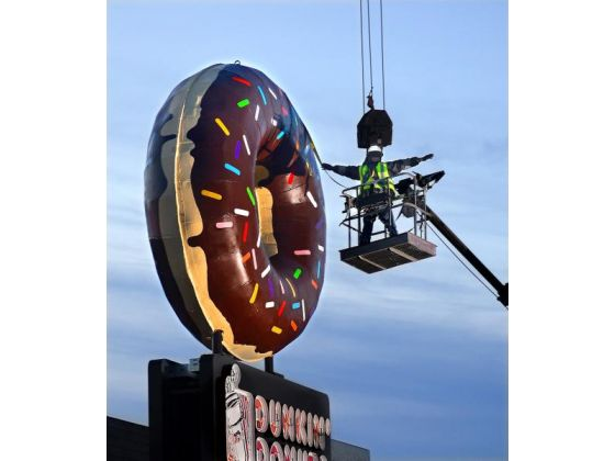 (newly restored donut being placed atop Dunkin Donuts on Monday, December 8)