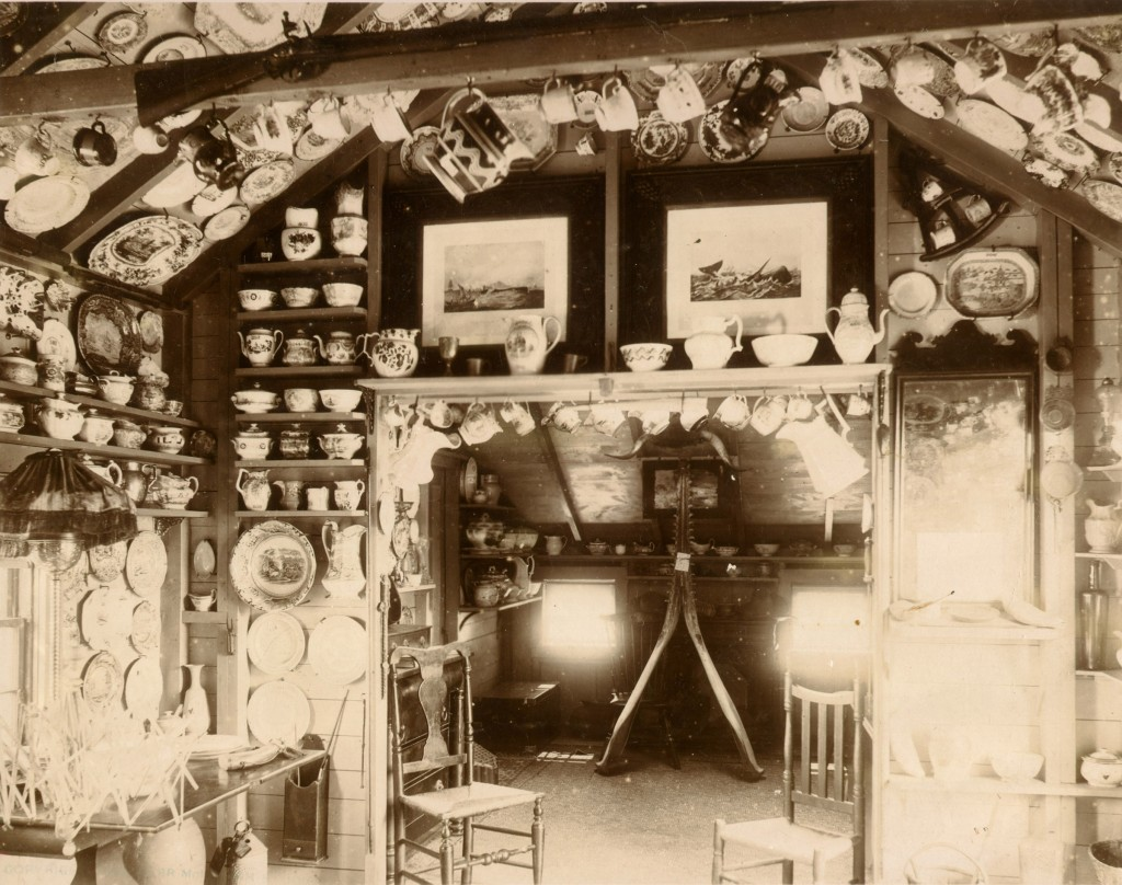 The cottage of Mrs. Evelyn Underhill, circa 1900. The walls and ceiling of the cottage interior were lined with china collections, dishes, and tea services.